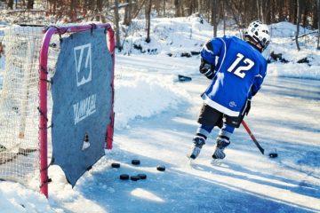 jeune qui fait du hockey avec sa crosse