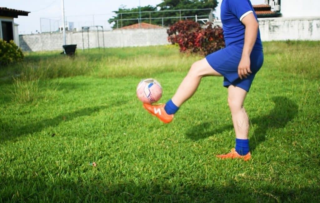 jeune s'entrainant au foot dans le jardin